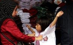 Seorang ibu memasangkan seragam baru SD pada anaknya di Pasar Mester Jatinegara, Jakarta Timur, Minggu (10/7/2017). Menjelang masuk sekolah sejumlah pedagang baju seragam sekolah dan buku tulis banyak diserbu para pembeli.